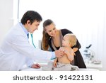 Surprised baby being checked by a doctor using a stethoscope - stock photo