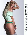 Provocative blonde girl in green underwear and provocative white shirt, posing - stock photo