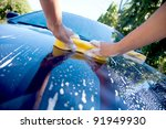2 hands hold sponge over the car for washing - stock photo