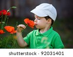 Cute little boy smells a wild flower - stock photo