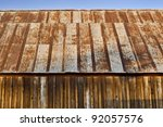side view of very old wooden barn with rusty roof, a little blue sky at the top - stock photo