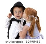 Adorable little boy holds on to his hat as a pretty little girl kisses his cheek - stock photo