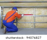 Construction worker thermally insulating house attic with mineral wool - stock photo