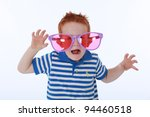 Cheeky fun red haired boy in blue striped shirt playing with large pink and purple sunglasses as a joke - stock photo