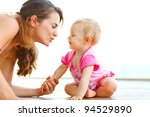 Young mother playing with baby on floor - stock photo
