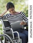 Black Woman in a wheelchair reading a Digital Tablet - stock photo