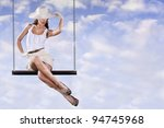 Woman with hat swinging on sky swing. Surreal concept - stock photo
