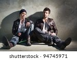Handsome young men, sitting on the floor, relaxed and confident. - stock photo