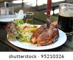 Traditional Czech pork knuckel on the bone speared with a knife - stock photo