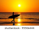 Surfer silhouette walking into the waves at sunrise - stock photo