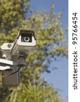 Focus is on the two security cameras with a tree in the background. - stock photo