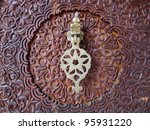 Moroccan style door knocker on an intricately carved wooden door - stock photo
