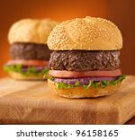Hamburgers on wooden board on an orange vignetted background. - stock photo
