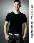 Young strong man in black t-shirt on gray background. - stock photo