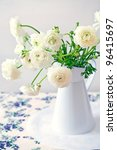 White Ranunculus in a flower vase on a table. - stock photo