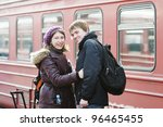Happy young couple waiting for train on railway station platform - stock photo