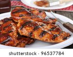 Barbecue grilled chicken breasts on a paper plate - stock photo