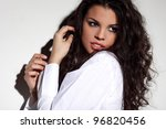 Portrait of attractive young brunette in white shirt posing sensually - stock photo