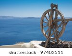Old wooden wheel in Oia Village, Landscape with caldera view on the background, Santorini Island, Greece. - stock photo