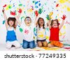 A group of cheerful kids with their palms and clothing painted - stock photo