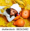 African american girl lying on pumpkin among yellow leaves - stock photo