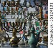 Background of the  retro and antique traditional Jewish holiday candlesticks with vintage jugs and old albums of stamps. Jerusalem flea market. - stock photo