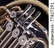 Close up of the keys and valves of a concert french horn set against a dark background - stock photo