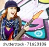 Closeup portrait of a happy young girl with guitar and graffiti on background - stock photo