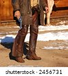 Cowboy in chaps & spurs holding revolver by side - stock photo