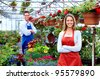Florists couple working with flowers at a greenhouse. - stock photo