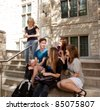 Group of university or college students sitting on steps, visiting and having fun - stock photo
