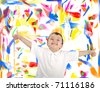 Kid with thumbs up against wall with colors on - stock photo