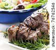 Lamb kebabs on rosemary skewers, with Greek salad behind. - stock photo