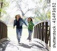 Two Girls Running Across a Bridge in a Park - stock photo